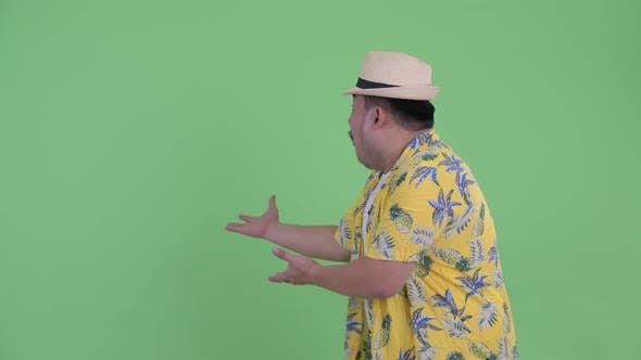 Thumbnail for Happy Young Overweight Asian Tourist Man Showing To Back and Looking Surprised