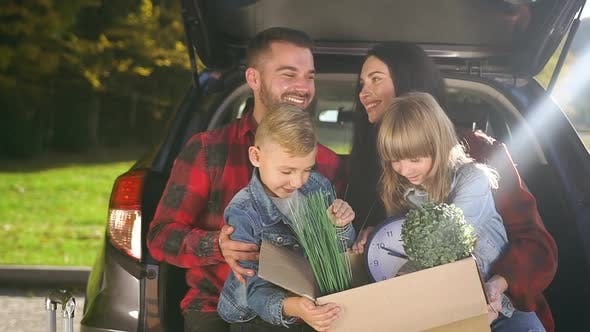 Thumbnail for Parents Holding on their Knees Cute Kids with Carton Box with Plants Before Moving Out