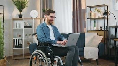 Man in Glasses Sitting in Wheelchair After Accident at Home and Working on Computer