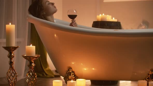 Thumbnail for Beautiful Girl in a Bathtub with Candles in Glasses on the Floor and Fluffy Feathers on a White
