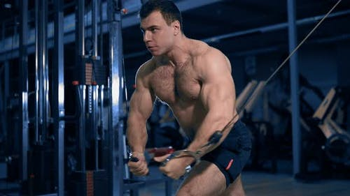 Bodybuilder Doing Exercise on the Simulator in the Gym