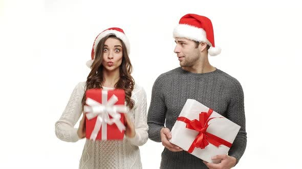Thumbnail for Young Couple Playing and Hiding Behind Christmas Present Box on White Isolated Background