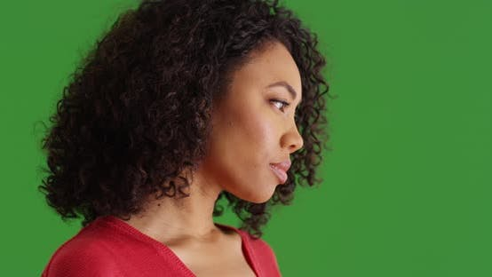 Thumbnail for Thoughtful black woman looking to the side turns toward camera on greenscreen