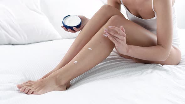 Body Skin Care. Woman Applying Body Cream On Leg Skin At Bedroom