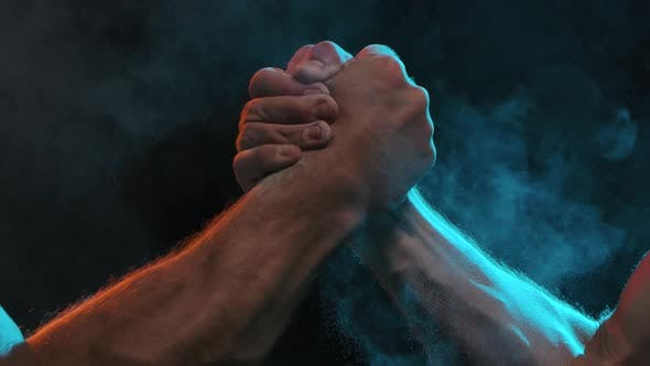 Sports Handshake of Two Muscular Men on a Black Background. Slow Motion. Close Up.
