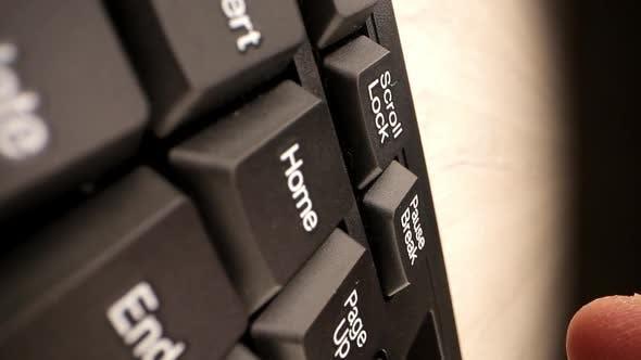 Person Finger Presses Black White Pause Break on Keypad