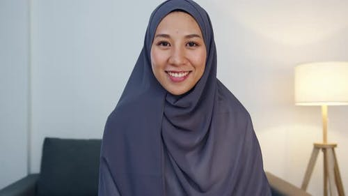 Muslim lady wear hijab using computer laptop talk to colleague about plan in video call meeting.