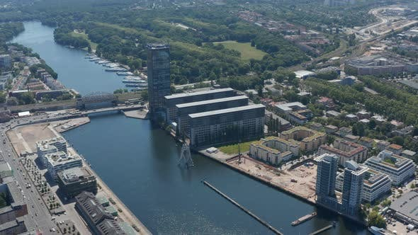 Aerial Footage of Molecule Man Sculpture on Spree River in From of Treptower Tall Building Complex
