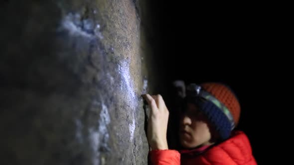 Thumbnail for Detail of a mans hands as he climbs boulders at night.