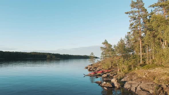 Kayaks at Bank of Large Lake Near Island with Pine Forest