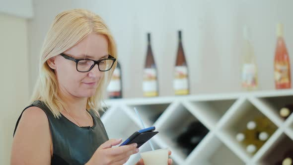 Young Woman in Elegant Black Dress Uses a Smartphone in the Tasting Room of the Winery
