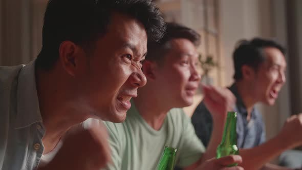 Three Asian Males Cheering And Watching Football Game On Tv And Celebrating Victory At Home
