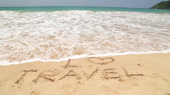 I LOVE TRAVEL written in the beach sand washed aways by waves.
