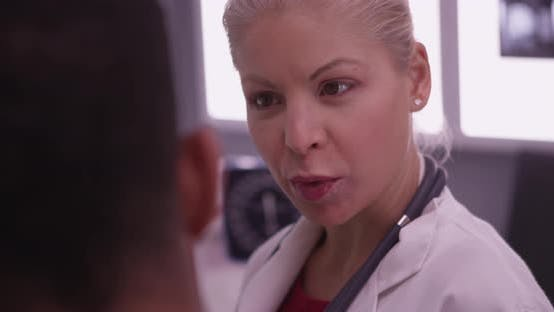 Thumbnail for Close up of white female physician talking to her patient in hospital