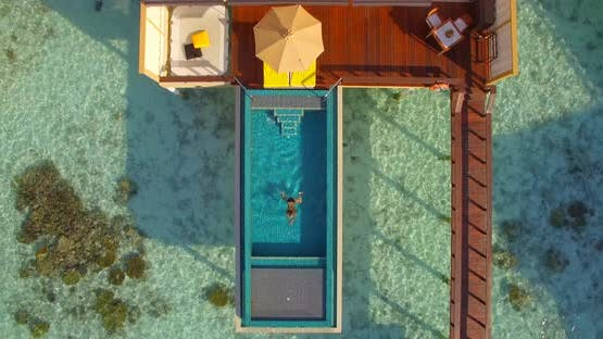 Aerial drone view woman swimming in pool of overwater bungalow on a tropical island resort hotel.