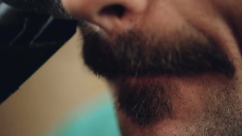 Male Carefully Grooming His Beard with Electric Shaver Extreme Closeup