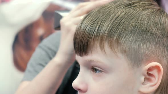 Thumbnail for Barber Cutting Boy's Hair with Clipper in Background