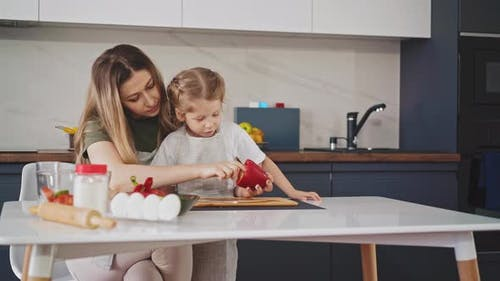 Pretty Mother with Child Sit in Kitchen