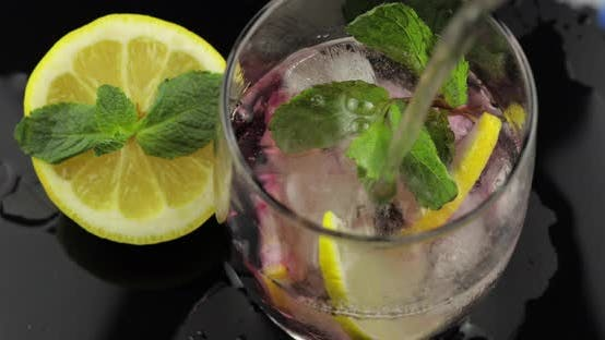Thumbnail for Pour Water in a Glass with Leaves of Mint, Lime, Lemon, Currants, Ice Cubes