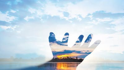 Double exposure with human hand and sky timelapse