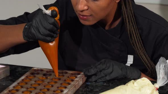Thumbnail for Mature Ethnic Woman Filling Chocolate Molds with Fruit Cream