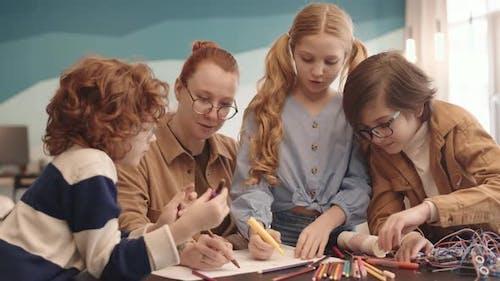 Teacher and Pupils Drawing Robot Scheme on Paper Sheet