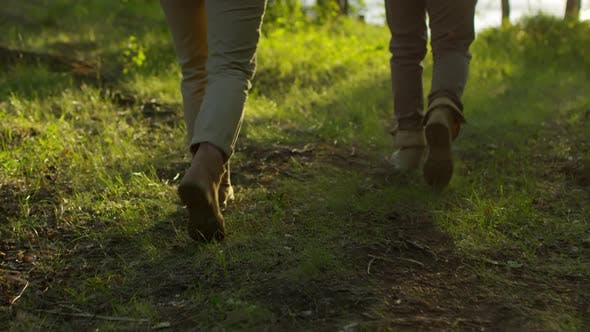 Thumbnail for Legs of Tourists Walking on Green Grass in Forest