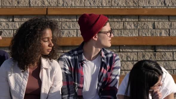 Thumbnail for Langweilige Schüler sitzen zusammen und schauen sich um