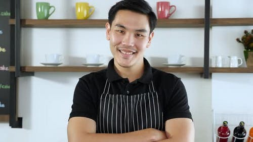 Portrait of Young asian male barista or waiter in polo shirt and apron smiling
