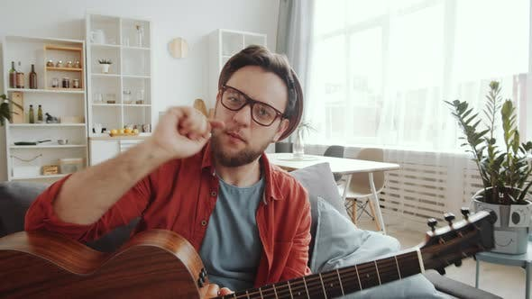 Male Musician Playing Guitar and Singing at Camera while Staying at Home