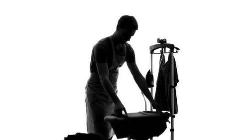 Smiling Male Householder Ironing Clothes on Board, Sharing of Housework Duties