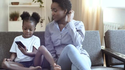Curly African American Mother and Little Girl Sitting at Home Sofa
