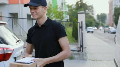 Courier Delivering Package To Client Outdoors