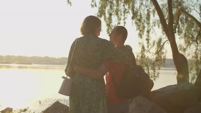 30s Husband and Wife Kissing on the Riverside on Sunrise