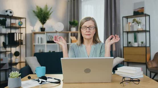 Senior Woman Meditating while Sitting at Table with Laptop