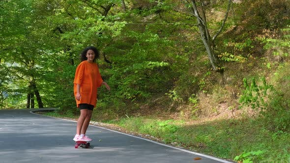Sporty Girl Spending Free Time in the Park and Skateboarding