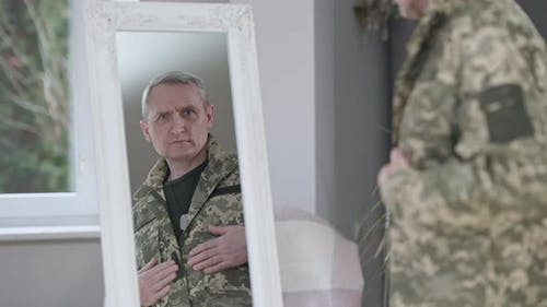 Reflection in Mirror of Confident Handsome Middle Aged Man Adjusting Military Uniform Indoors