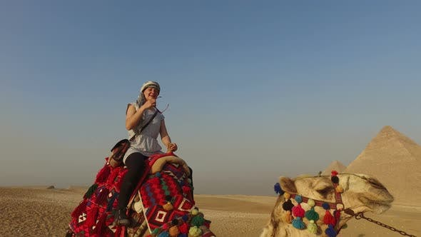 Woman riding camel in front of Giza pyramids