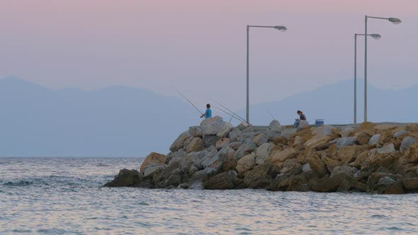 Thumbnail for Man Fishing in the Sea From Rocky Pier, Evening Scene
