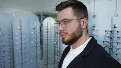 Man Trying Eyeglasses In Optics Store.