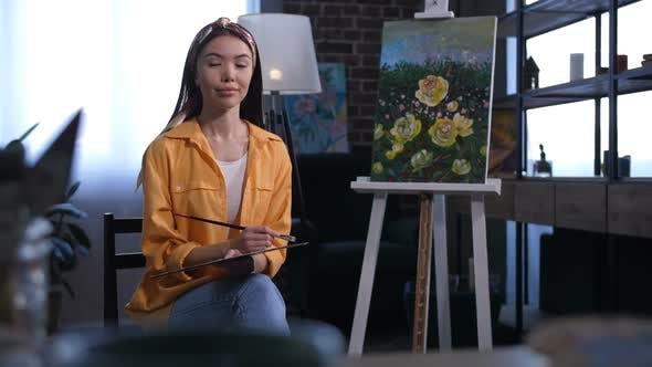 Attractive Asian Female Artist Sitting Near Canvas
