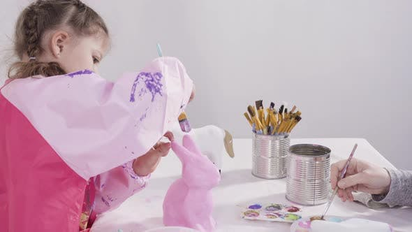 Little girl painting paper mache figurines with acrylic paint  for her homeschooling art project