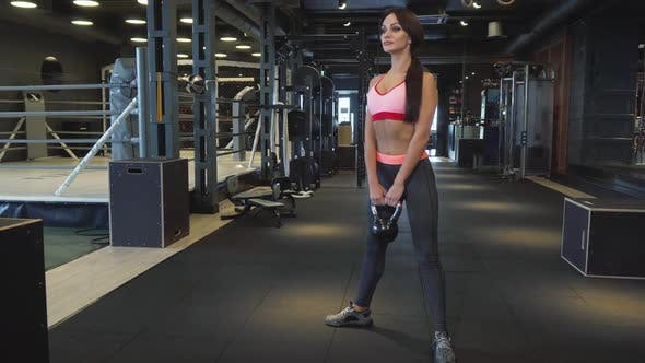 Thumbnail for A Girl with an Ideal Figure Performs Squats with Dumbbells