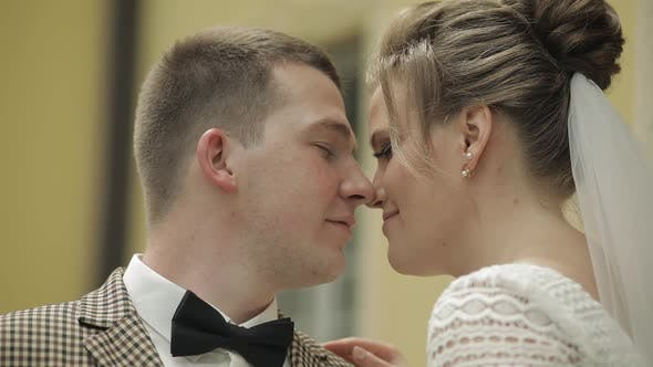 Newlyweds. Caucasian Groom with Bride Making a Kiss. Wedding Couple. Man and Woman in Love