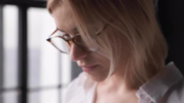 Close Up A Young Blonde Business Woman With Glasses Makes A Business Plan Communicates