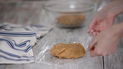 Women's Hands Wrap the Dough in Plastic Wrap