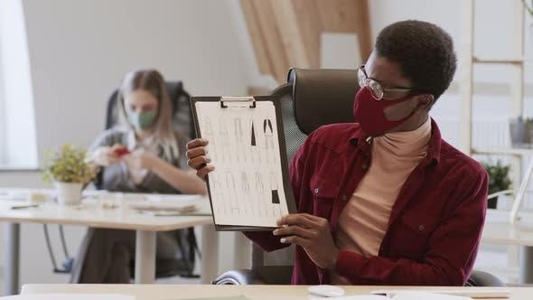 Male African-American Designer Wearing Mask Having Video Talk