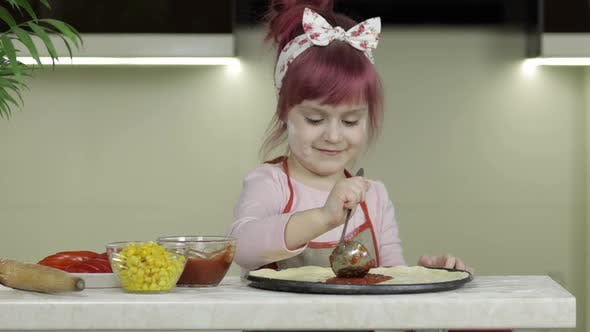 Thumbnail for Cooking Pizza. Little Child in Apron Adding Tomato Sauce To Dough in Kitchen