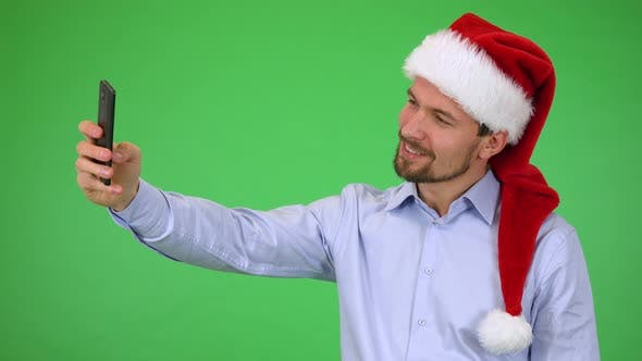 Thumbnail for A Young Handsome Man in a Christmas Hat Takes Selfies with a Smartphone - Green Screen Studio