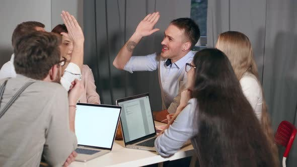 Group of Young Marketing Specialists Are Cheerfully Meeting in Office